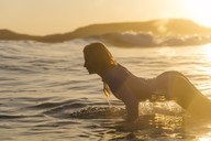 Female surfer in sea at sunset - AURF06074