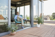 Young man sitting in armchair at balcony door - RBF06799