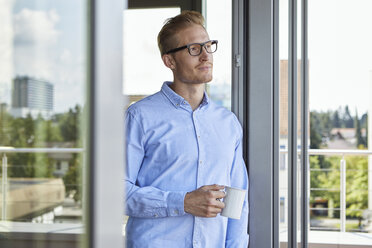 Young man with cup of coffee standing at balcony door - RBF06802