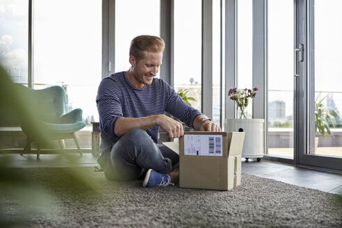 Smiling young man sitting on carpet at home unpacking parcel - RBF06826