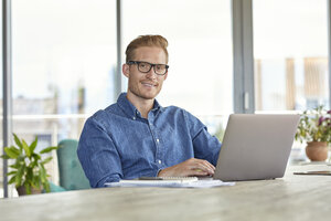 Portrait of smiling young man sitting at table using laptop - RBF06835