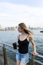 Young woman looking over East River, holding cup of coffee - GIOF04506