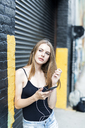 Young woman leaning on street corner, listening music, using smartphone - GIOF04518