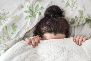 Woman lying in bed covering her face with blanket - FLMF00062