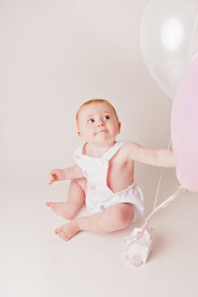 Portrait of baby girl with balloons and birthday present - NMS00256