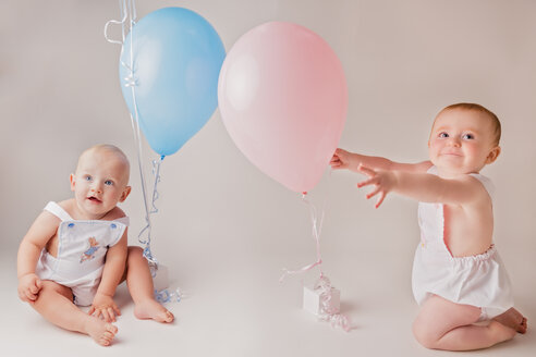 Portrait of baby boy and baby girl  with balloons and birthday presents - NMS00259