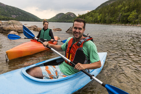 Couple smiling at camera while kayaking on Jordan Pond in Acadia National Park, Maine, USA - AURF06169