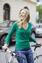 Young woman with bicycle in the city - PNEF00971