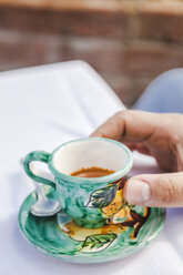 Man's hand holding a cup of espresso - FLMF00080