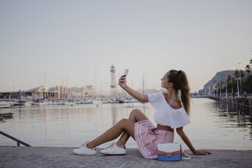 Fashionalble young woman sitting at the harbour of Barcelona, using smartphone - AFVF01610
