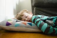 Tired boy sleeping on floor at home - CAVF48760