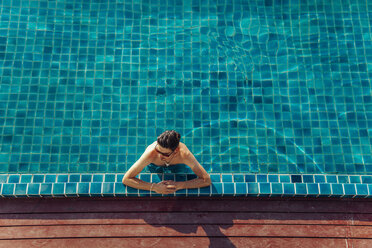 High angle view of shirtless man relaxing in swimming pool at tourist resort - CAVF48775