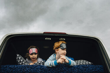 Siblings with sleep masks lying in vehicle while looking away against cloudy sky - CAVF48790