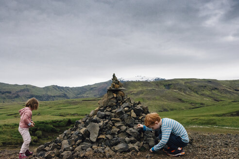 Siblings playing by heap of rocks on field against cloudy sky - CAVF48796