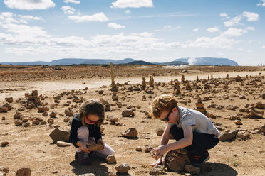 Siblings playing with rocks at desert during sunny day - CAVF48799