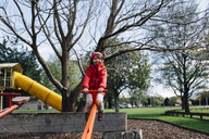 Playful girl wearing raincoat sitting on seesaw at playground - CAVF48802