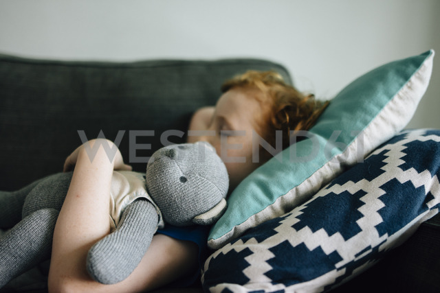 Side view of boy sleeping with teddy bear on couch at home - CAVF48811