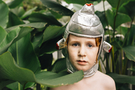 Close-up portrait of shirtless boy wearing headwear costume by plants at backyard - CAVF48820