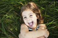High angle portrait of happy girl lying on grassy field at park - CAVF48826