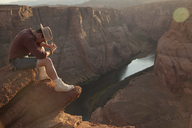 Full length of young man sitting on rock by Horseshoe Bend at desert - CAVF48841