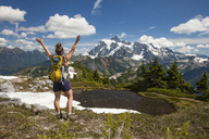 Rear view of female hiker with backpack standing at North Cascades National Park - CAVF48874