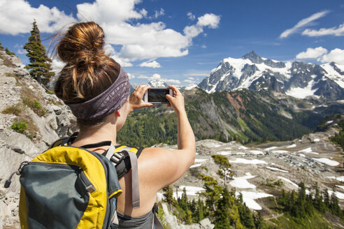 Rear view of hiker photographing with mobile phone on mountain at North Cascades National Park - CAVF48877