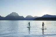 Female friends paddleboarding on lake against clear sky at Grand Teton National Park - CAVF48892