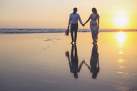 Newlywed couple holding hands while walking at beach against clear sky during sunset - CAVF48901