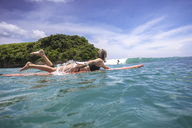 Friends surfing on sea against sky at Bali - CAVF48910