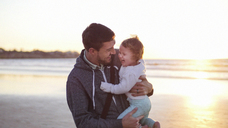 Happy father carrying daughter while standing at beach against clear sky during sunset - CAVF48937