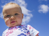 Low angle portrait of cute baby girl standing against blue sky during sunny day - CAVF48940