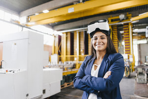Young woman working in distribution warehouse, wearing VR glasses - KNSF04797