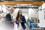 Businessman an woman in high tech enterprise, having a meeting in factory workshop - KNSF04833