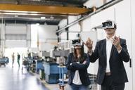 Businessman an woman in high tech enterprise, using VR glasses - KNSF04839