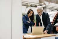 Businessman an woman in high tech enterprise, having a meeting, using laptop - KNSF04845
