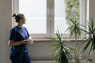 Young woman working in high tech enterprise, taking a break, drinking coffee - KNSF04851