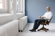 Manager sitting in chair in his office, looking out of the window, thinking - KNSF04866