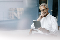 Manager sitting in office, using digital tablet - KNSF04869