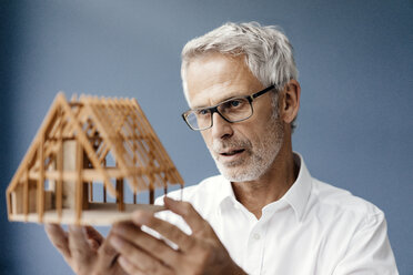 Successful architect looking at model of a house - KNSF04872