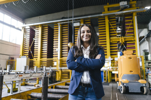 Confident woman standing in logistics center, with arms crossed - KNSF04881