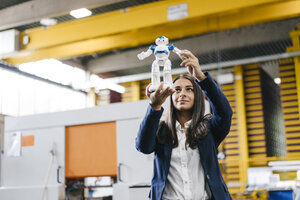 Young woman working in distribution warehouse, looking at toy robot - KNSF04884
