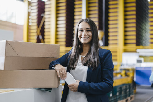 Young woman working in distribution warehouse - KNSF04893