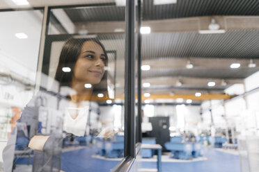 Confident woman working in high tech enterprise, looking out of control room - KNSF04902