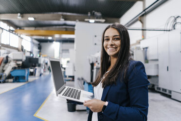 Confident woman working in high tech enterprise, holding laptop - KNSF04905