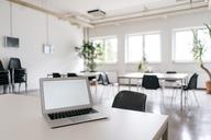 Laptop with blank screen on desk in board room - KNSF04929