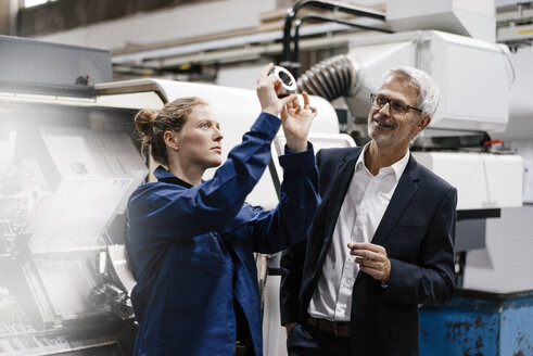 Manager and skilled worker in high tech enterprise, checking machine parts - KNSF04935