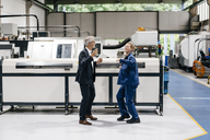 Manager and skilled worker dancing in factory workshop, having fun - KNSF04941