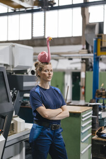 Young woman working as a skilled worker in a high tech company, balancing a pink flamingo on her head - KNSF04953