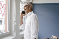 Manager standing by window with a heart-shape on it, talking on the phone - KNSF04956