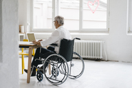 Handicapped manager in a wheelchair, working in office - KNSF04959